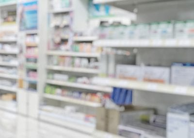 Pharmacy store or drugstore blur background with drug shelf and blurry pharmaceutical products, cosmetic and medication supplies on shelves inside retail shop interior