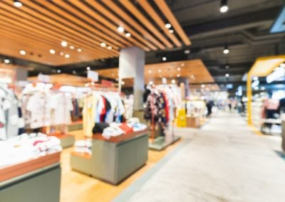 Blurred, defocused background of clothing shops in modern shopping mall or department store. Shopaholic lifestyle, or fashion dress outlet business concept